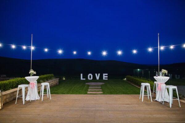 White-Tolix-Stools-Stainless-Steel-Bar-Table-White-Linen-Festoon-Lighting-String-on-Lighting-Poles-Seacliff-House